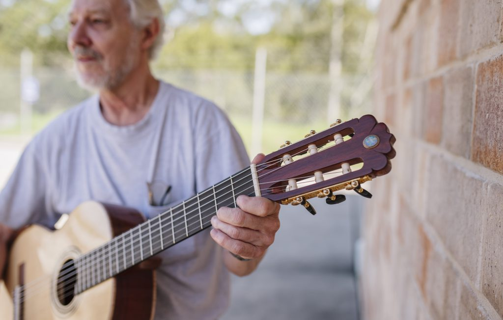 Close up of man holding guitar