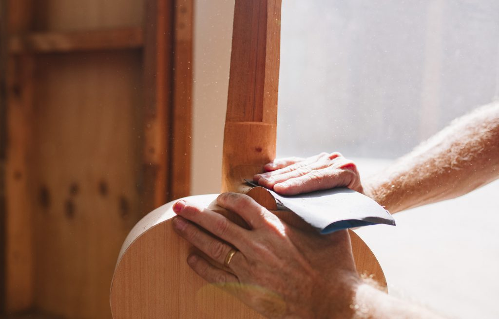 Hand sanding acoustic guitar